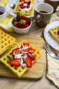 Waffle garnished with strawberries, Greek yogurt and almonds on breakfast table - GIOF03962