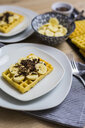 Waffle garnished with banana and chocolate shaving on plate - GIOF03965