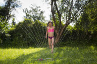 Little girl having fun with lawn sprinkler in the garden - LVF07054