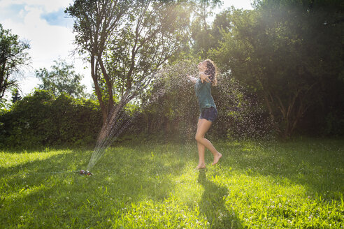 Girl having fun with lawn sprinkler in the garden - LVF07057