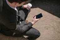 Over the shoulder view of young businessman reading smartphone texts - CUF27111
