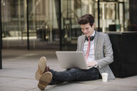 Young city businessman sitting on sidewalk using laptop - CUF27123