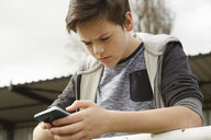 Anxious teenage boy reading smartphone text message - CUF27147