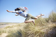 Young boy on beach, wearing fancy dress, leaping into air - CUF27225