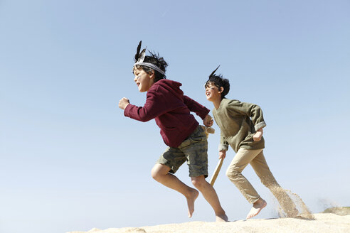 Two boys, wearing fancy dress, playing on sand - CUF27267