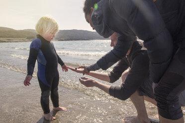 Boy and parents on beach, Loch Eishort, Isle of Skye, Scotland - CUF27348