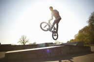 Young man, in mid air, doing stunt on bmx at skatepark - CUF27357