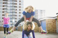 Three women exercising together wearing sports clothing and playing leap frog - CUF27360