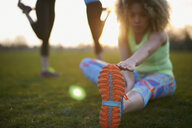 Portrait of woman stretching before exercise in park - CUF27366