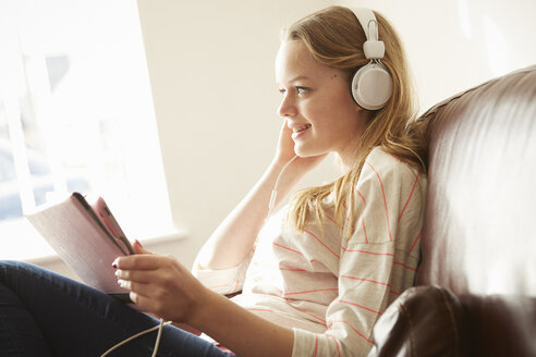 Girl on sofa wearing headphones listening to music from digital tablet - CUF27561