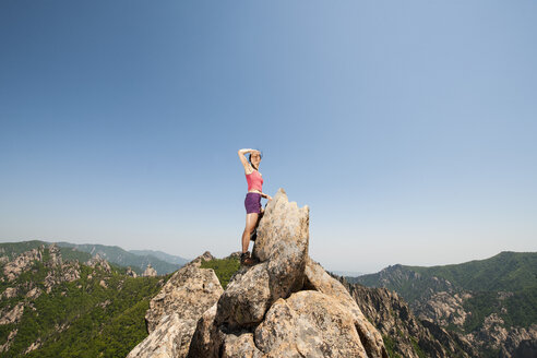 Female hiker looking out from rock formation on way to Daecheongbong peak,  Seoraksan National Park in South Korea - CUF27606