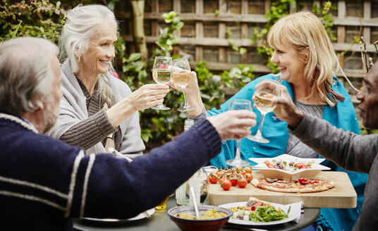 Senior friends making a toast during meal in garden - CUF27648