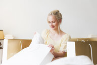 Beautiful young woman on bed unpacking shopping bags - CUF27702