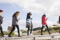 Row of young adult friends strolling along beach boardwalk reading smartphones, Western Cape, South Africa - CUF27729
