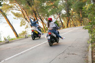 Rear view of two couples riding mopeds on rural road, Split, Dalmatia, Croatia - CUF27765