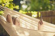 Teenage boy reclining in garden hammock browsing digital tablet - CUF27768
