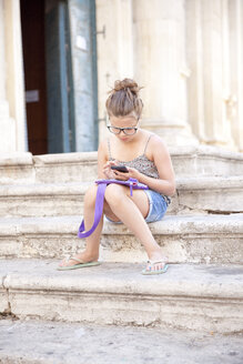 Young girl using mobile phone on steps, Lecce, Italy - CUF27783