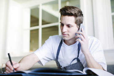 Young male chef doing paperwork and talking on smartphone in restaurant - CUF27801