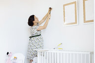 Pregnant mid adult woman hammering nail for picture frame in childs nursery - CUF27819