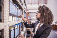 Young businesswoman searching office shelves - CUF27886