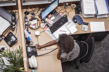 Overhead view of businesswoman talking on landline at office desk - CUF27904