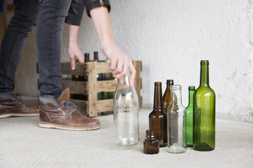 Teenage boy placing empty bottles into wooden crate in garage - CUF28000