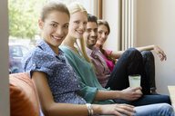Portrait of young adults friends on cafe sofa - CUF28060