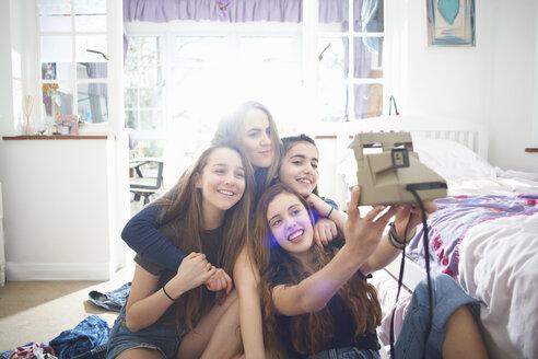 Four teenage girls taking instant camera selfie in bedroom - CUF28110