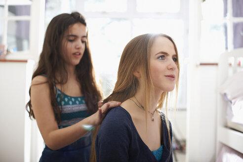 Teenage girl having hair plated by best friend in bedroom - CUF28119