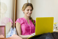 Young woman using yellow laptop in cafe - CUF28125