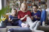 Mother and her daughters sitting on couch, having fun  using digital laptop and playing with smartphones - RBF06243