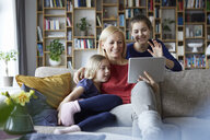 Mother and her daughters sitting on couch, having fun  using digital laptop - RBF06252