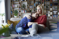 Mother and adolescent daughter sitting on couch with arms around - RBF06255
