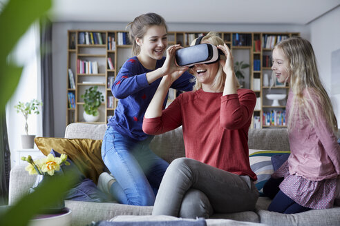 Daughters showing mother how to play with VR glasses - RBF06258