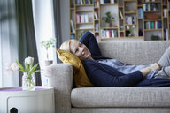 Woman relaxing at home, lying on couch - RBF06264