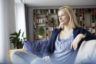 Woman relaxing at home, sitting on couch - RBF06267