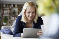 Woman using digital tablet, relaxing on couch - RBF06270