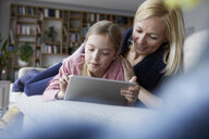 Mother and daughter lying on couch, using digital tablet - RBF06273
