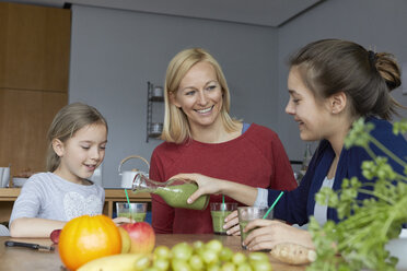 Mother with daughters sitting in kitchen, drinking homemade fruit smoothie - RBF06279