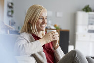 Happy woman relaxing at home, drinking coffee - RBF06291