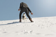 Man playing with dog in winter, having fun in the snow - REAF00271