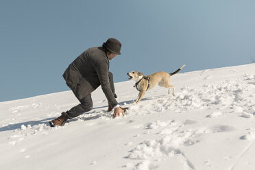 Man playing with dog in winter, throwing snow - REAF00277