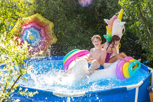 Brother and sister with oversized unicorn swim toy in paddling pool - SARF03778