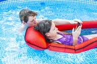 Brother and sister in swimming pool looking at smartphone - SARF03781