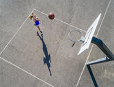 Aerial view of young woman playing basketball - STSF01605
