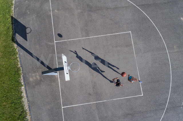 Young man and woman playing basketball, aerial view - STSF01608
