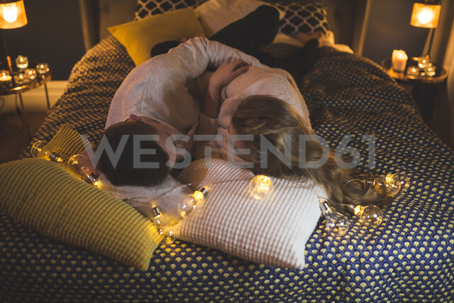 Romantic young couple cuddling in bed with fairy lights - AWF00047 - Inner Vision Pro/Westend61