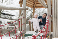 Mother and little daughter on climbing frame in winter - DIGF04580