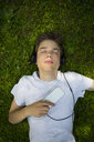 Portrait of boy lying on meadow listening music with headphones and smartphone - LVF07076