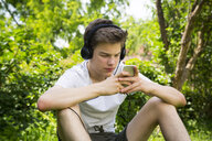 Boy sitting in the garden listening music with headphones and smartphone - LVF07079